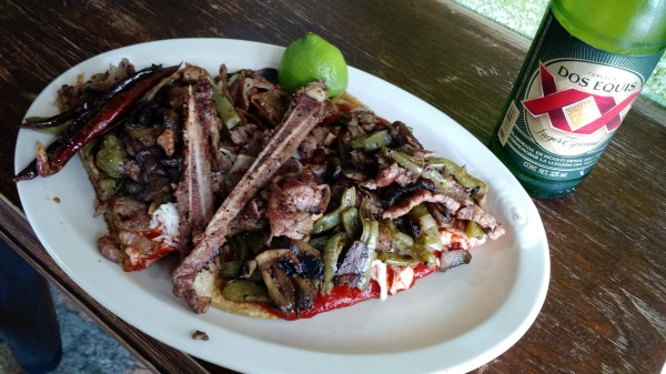Huarache de costilla con guacamole y salsa roja, nopales y chela